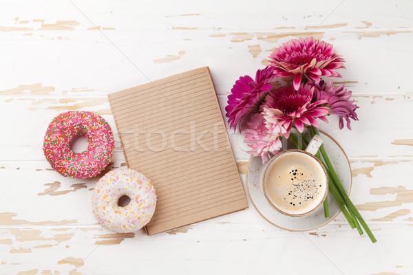 Coffee cup, donuts and gerbera flowers Stock photo © karandaev