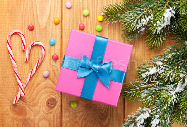 Gift box over christmas wooden background with snow fir tree Stock photo © karandaev