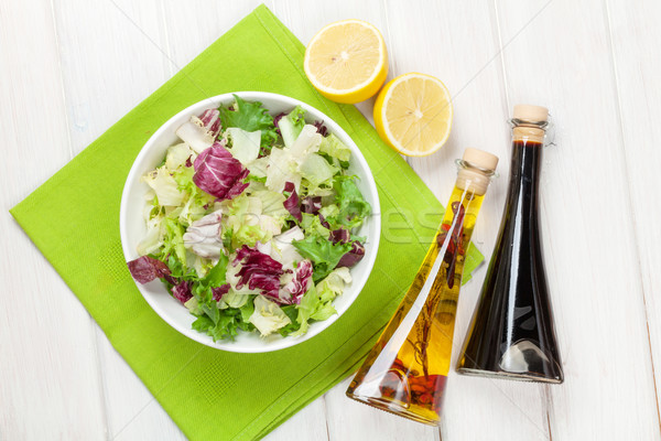 Fresh healthy salad and condiments over white wooden table Stock photo © karandaev