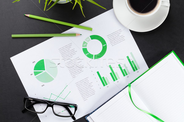 Office desk with charts, coffee, plant and notepad Stock photo © karandaev