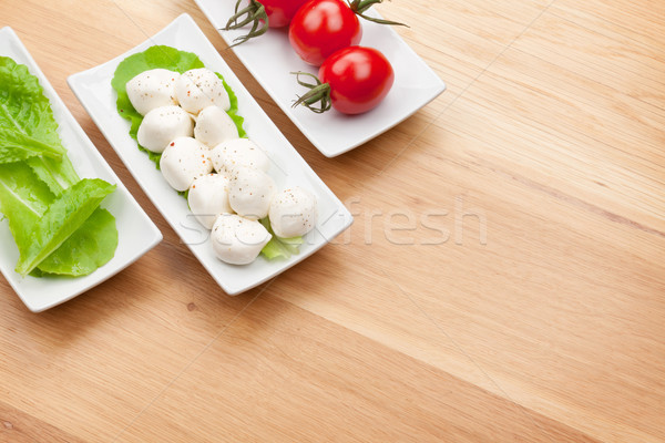 Tomatoes, mozzarella and green salad leaves Stock photo © karandaev
