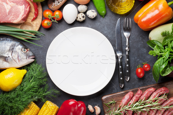 Empty plate surrounded by cooking ingredients Stock photo © karandaev