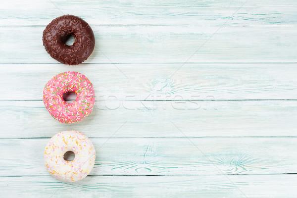 Coloré donuts table en bois haut vue espace de copie Photo stock © karandaev