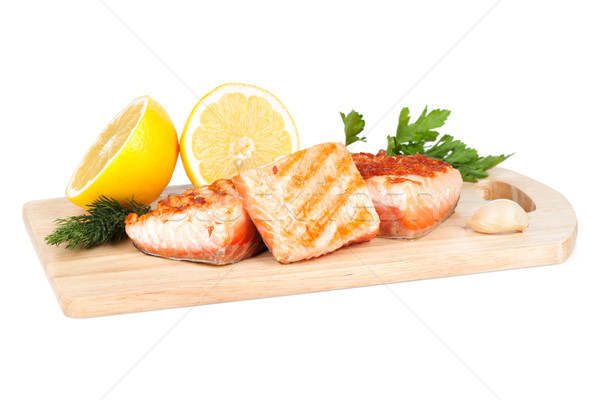 Grilled salmon with lemon and herbs on cutting board Stock photo © karandaev