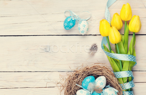 Easter background with blue and white eggs in nest and yellow tu Stock photo © karandaev