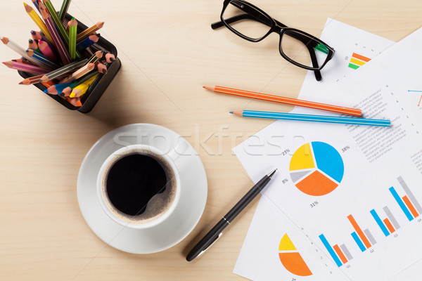 Office desk workplace with coffee cup and charts Stock photo © karandaev