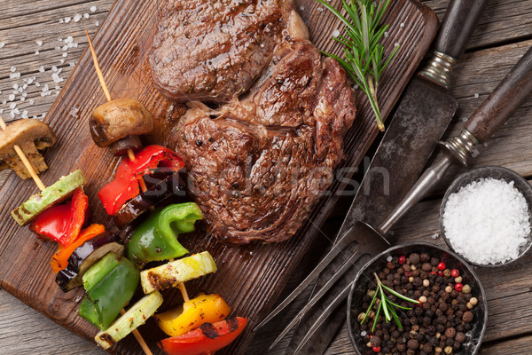 Stock photo: Beef steak and grilled vegetables on cutting board
