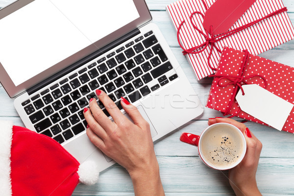Female working on laptop and wrapping gifts Stock photo © karandaev