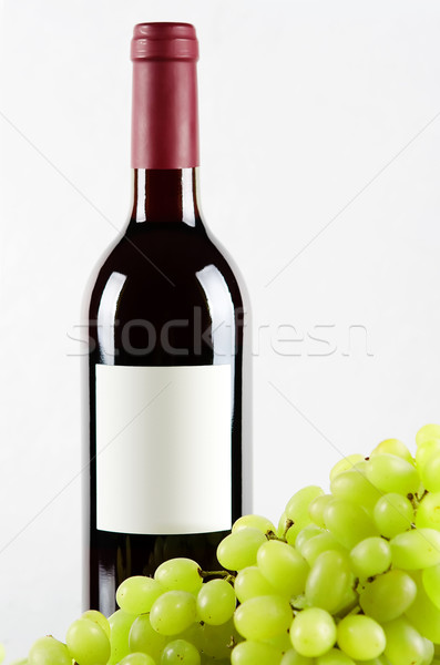 Bottle of red wine and green grapes in front Stock photo © karandaev
