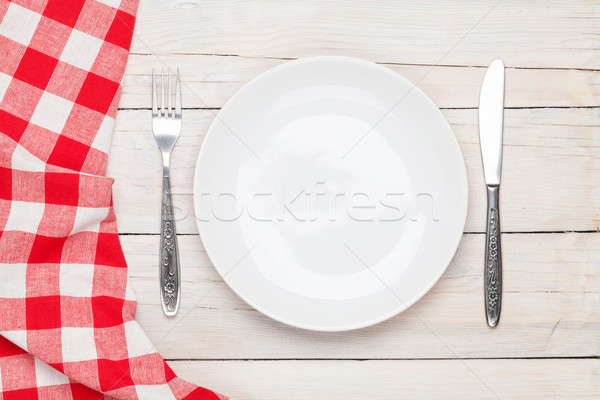 Empty plate, silverware and towel over wooden table background Stock photo © karandaev