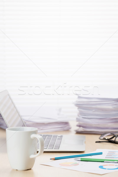 Office workplace with coffee cup, laptop and supplies Stock photo © karandaev