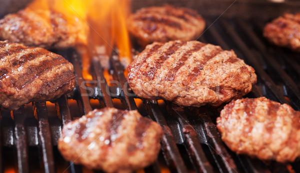 Burgers cooking on grill Stock photo © karandaev