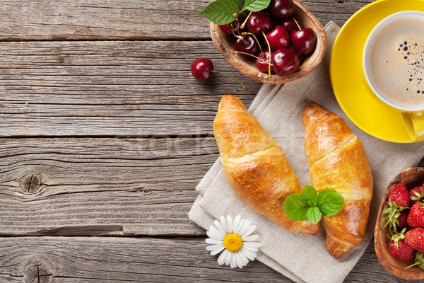Croissants and coffee cup on wooden table Stock photo © karandaev