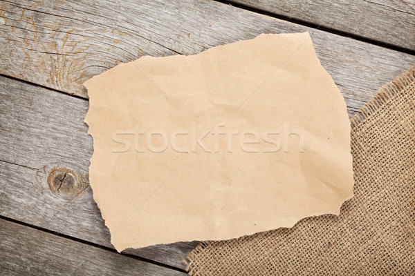 Old paper piece and burlap on wooden textured background Stock photo © karandaev