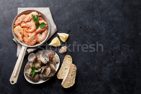 Stock photo: Fresh seafood on stone table. Scallops and shrimps
