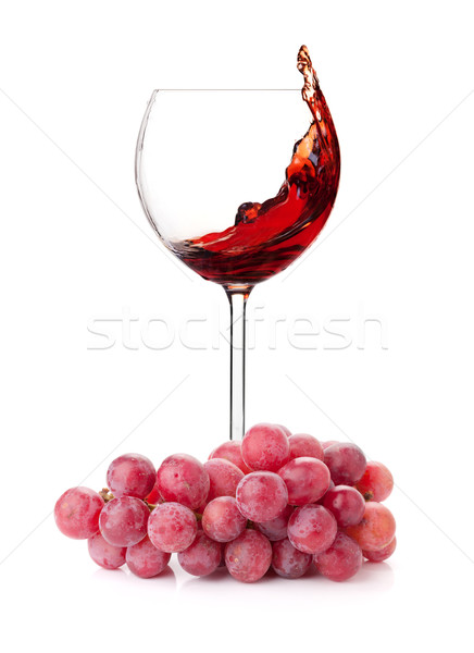 Stock photo: Splashing red wine in a glass and grapes