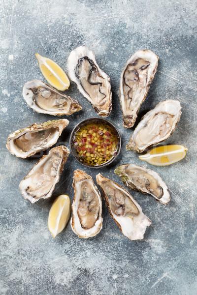 Fresh oysters on stone table Stock photo © karandaev