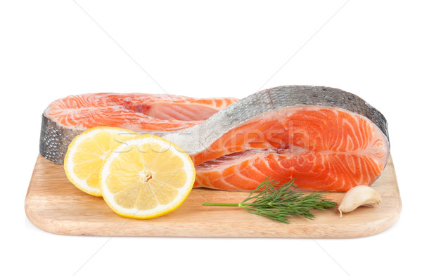 Salmon steaks on cutting board with lemons and herbs Stock photo © karandaev