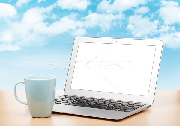 Laptop with blank screen and cup on table Stock photo © karandaev