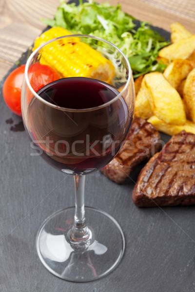 Red wine glass and steak with grilled potato, corn, salad Stock photo © karandaev