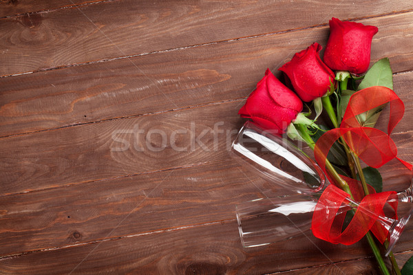 Red roses and champagne glasses Stock photo © karandaev