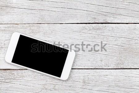 White smartphone on wooden table Stock photo © karandaev