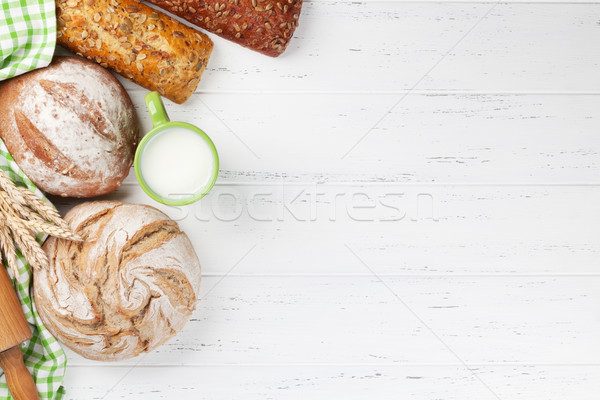 Stock photo: Various crusty bread and cup of milk
