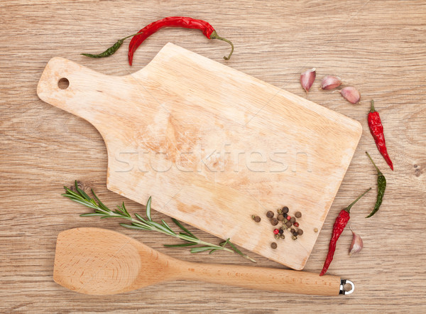 Cutting board with spices around over wooden table Stock photo © karandaev