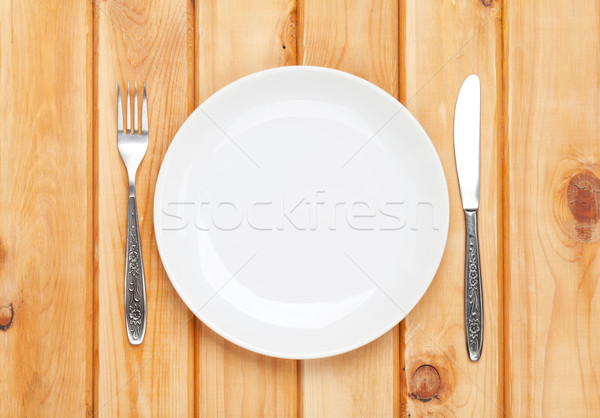 Empty plate and silverware over wooden table background Stock photo © karandaev