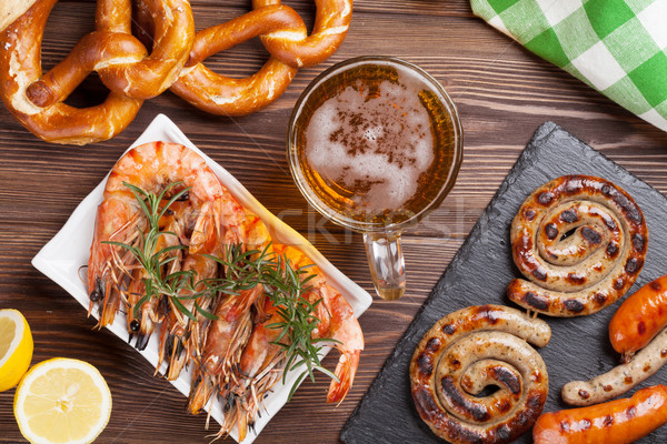 Beer mug, grilled shrimps, sausages and pretzel Stock photo © karandaev