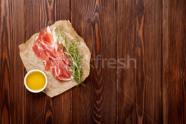 Prosciutto biberiye zeytinyağı ahşap masa üst görmek Stok fotoğraf © karandaev