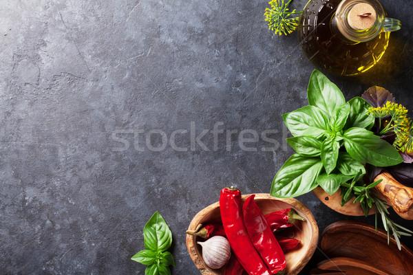 Fresh garden herbs in mortar, chili and oil Stock photo © karandaev