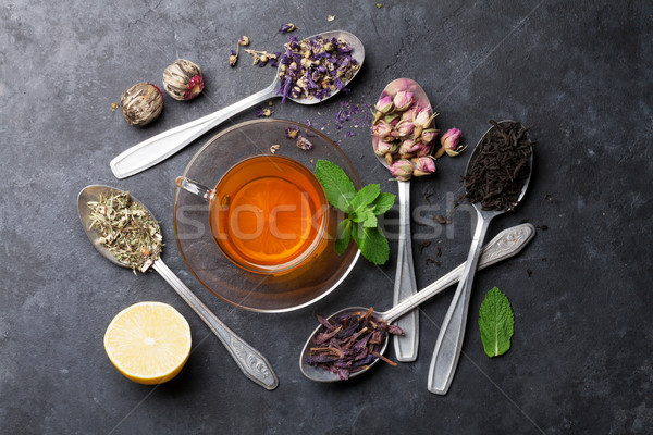Stock photo: Tea cup and assortment of dry tea in spoons