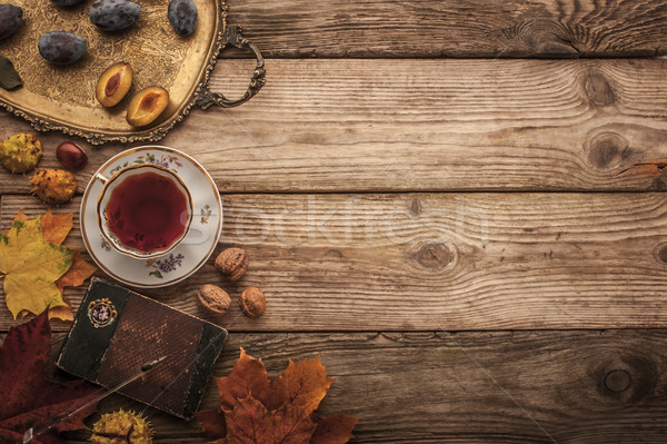 Plums , nuts and leaves with vintage notebook and tea with film  Stock photo © Karpenkovdenis