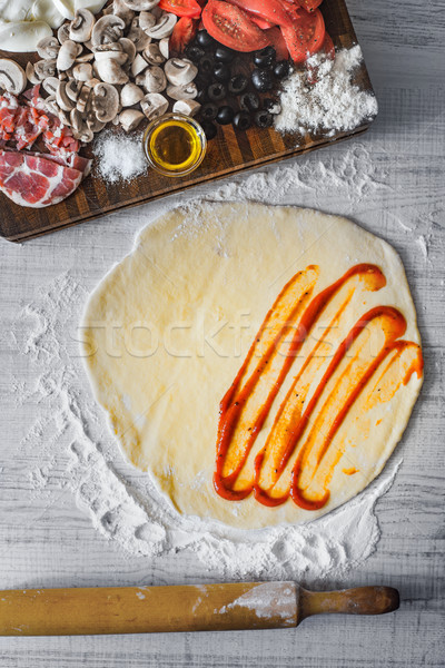 Dough with tomato sauce and ingredient for calzone top view Stock photo © Karpenkovdenis