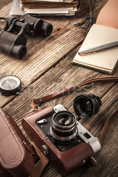 Camera with notebook and binoculars on the wooden table vertical Stock photo © Karpenkovdenis