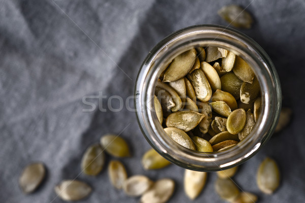 Stock photo: Pumpkin seeds in the glass jar cloth-up