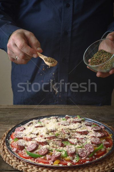 Man in a blue shirt sprinkle with spice pizza from a glass sauser Stock photo © Karpenkovdenis