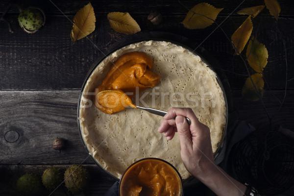 Putting  pumpkin puree on the dough for pumpkin pie horizontal Stock photo © Karpenkovdenis