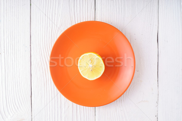 Half of lemon on orange plate Stock photo © Karpenkovdenis
