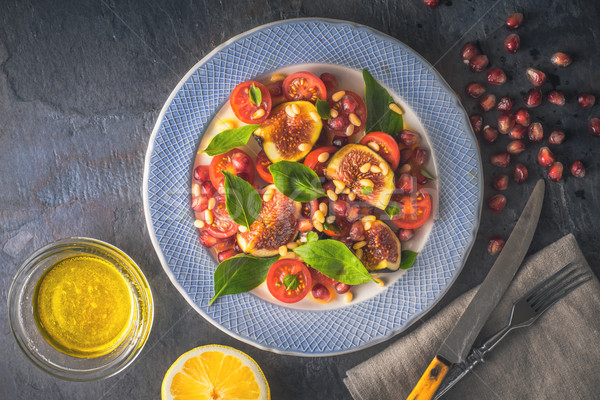 Fruit salad with fig and cherry tomatoes on the ceramic plate  on the stone table horizontal Stock photo © Karpenkovdenis