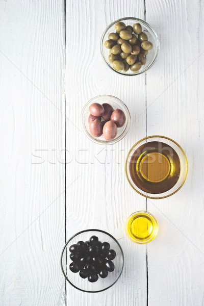Different olives and olive oil on the white wooden table top view Stock photo © Karpenkovdenis