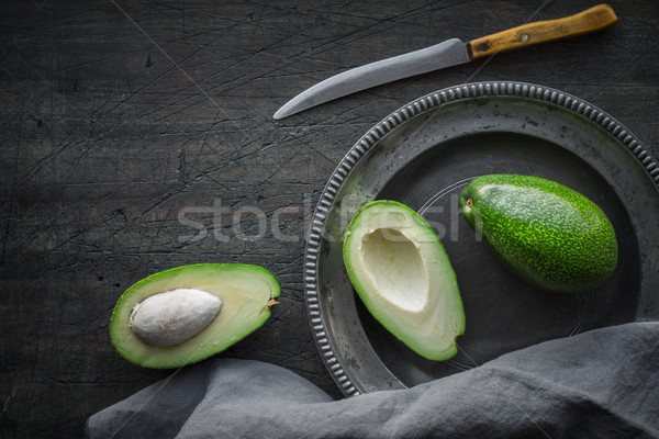 Avocado in the metal plate on the dark scratched table top view Stock photo © Karpenkovdenis