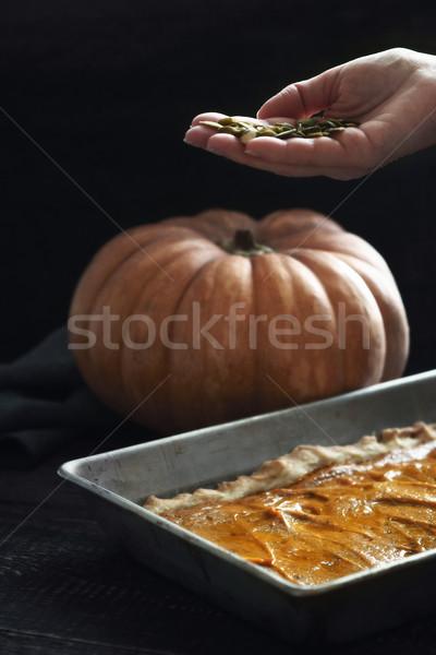 Adding pumpkin seeds in the pumpkin pie Stock photo © Karpenkovdenis