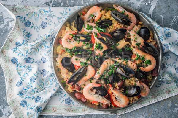 Paella in the metal plate on the  beautiful napkin top view Stock photo © Karpenkovdenis