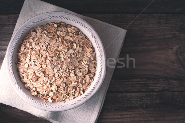 Raw oat flakes in  the bowl on the wooden table top view Stock photo © Karpenkovdenis