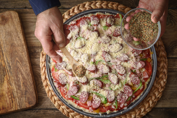 Man sprinkle with spice pizza from a glass sauser in a form Stock photo © Karpenkovdenis