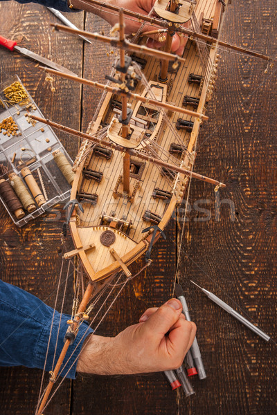 Man collects the vehicle model on the wooden table Stock photo © Karpenkovdenis