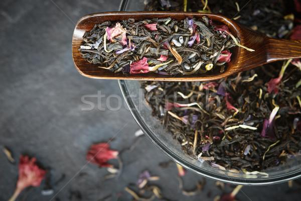 Black tea with flower  petals in the wooden spoon top view Stock photo © Karpenkovdenis