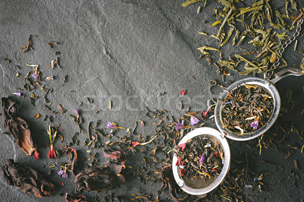 Different tea leave and strainer on the dark stone table top view Stock photo © Karpenkovdenis